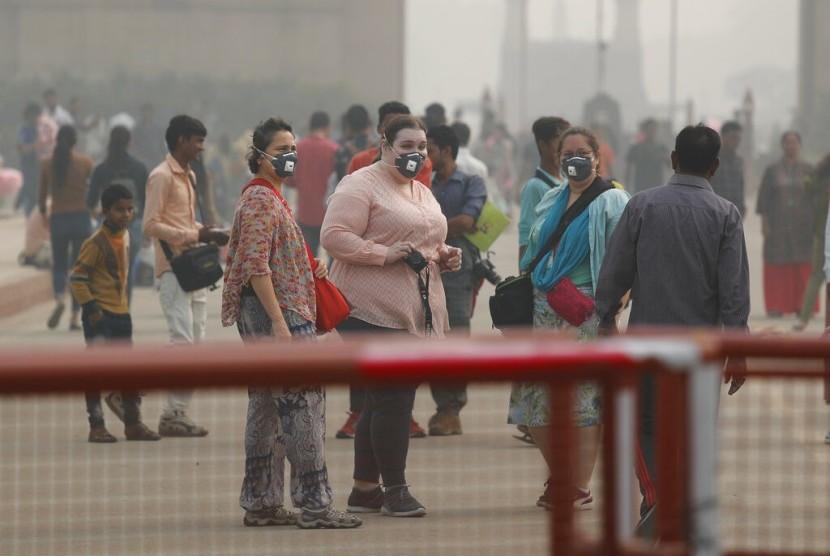 Warga India dan turis mengenakan masker untuk menghalau polusi udara saat berjalan di New Delhi, India, Senin (4/11).  India merupakan negara ketiga penghasil emisi terbesar di dunia. Ilustrasi.