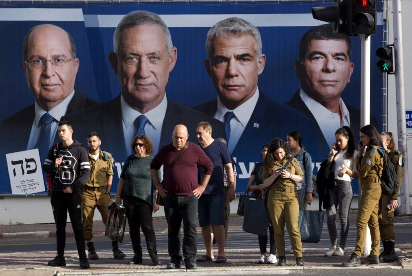 Warga Irael menunggu lampu lalu lintas menyala hijau di depan poster para pemimpin Partai Blue and White, (dari kiri ke kanan) Moshe Yaalon, Benny Gantz, Yair Lapid dan Gabi Ashkenazi, di Ramat Gan, Israel, Ahad (7/4).