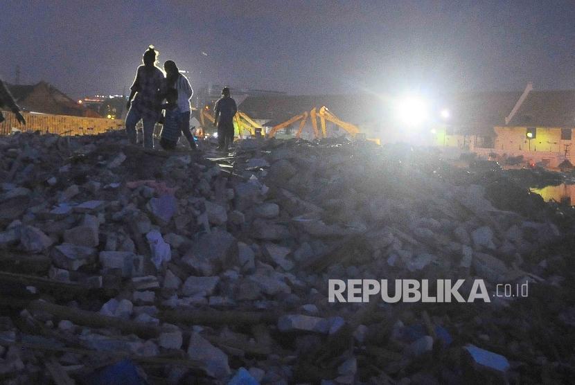 Warga Kampung Luar Batang korban penggusuran melintas diantara reruntuhan di Penjaringan, Jakarta Utara, Selasa (19/4). (Republika/Agung Supriyanto)