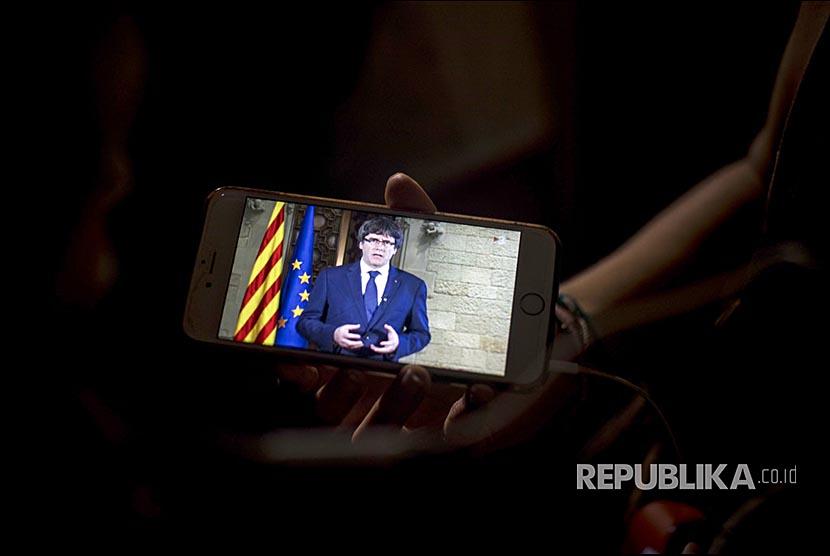 Warga Katalunya mendengarkan pidato President Carles Puigdemont pada ponsel di luar Gedung Palau Generalitat di Barcelona.