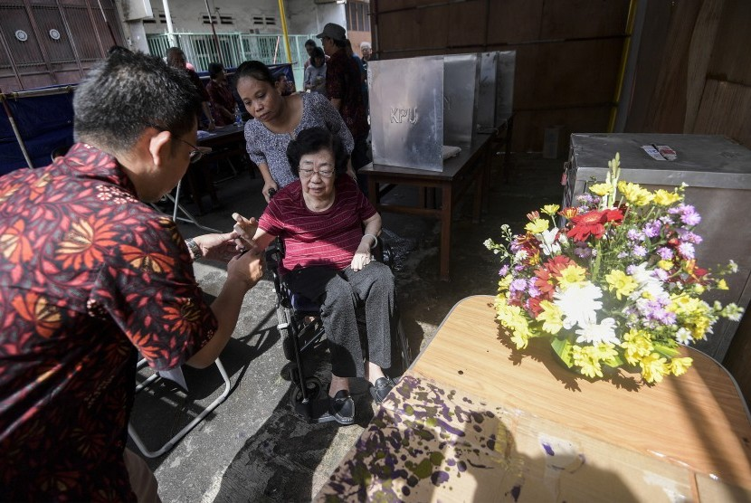 Warga keturunan Tionghoa mencelupkan jari ke dalam tinta usai memberikan hak suara dalam Pilkada DKI Jakarta di TPS 4 Glodok, Tamansari, Jakarta Barat, Rabu (15/2).