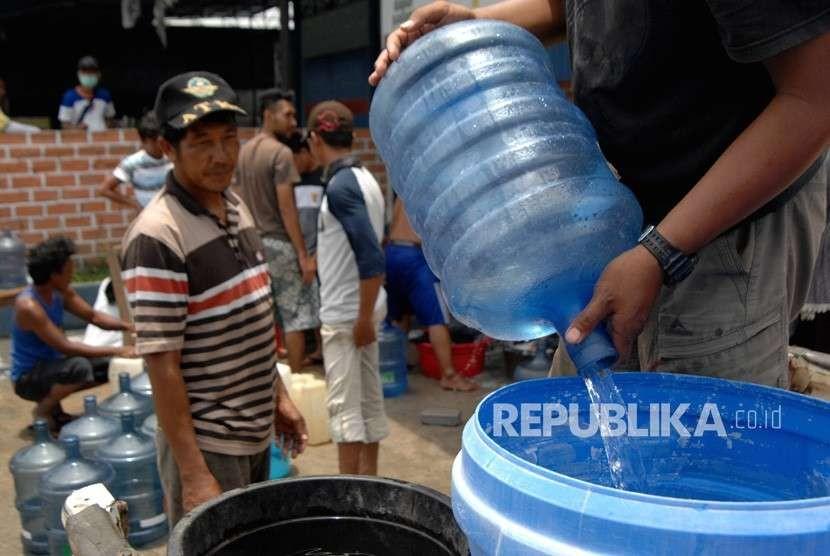 Warga korban gempa bumi Palu mengambil air di salah satu rumah warga di Pertigaan Petobo Palu, Sulawesi Tengah, Kamis (4/10).
