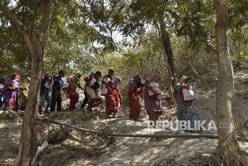 Warga korban gempa dan tsunami membawa bantuan dari Persiden Joko Widodo di Desa Loli Saluran, Donggala, Sulawesi Tengah, Rabu (3/10).