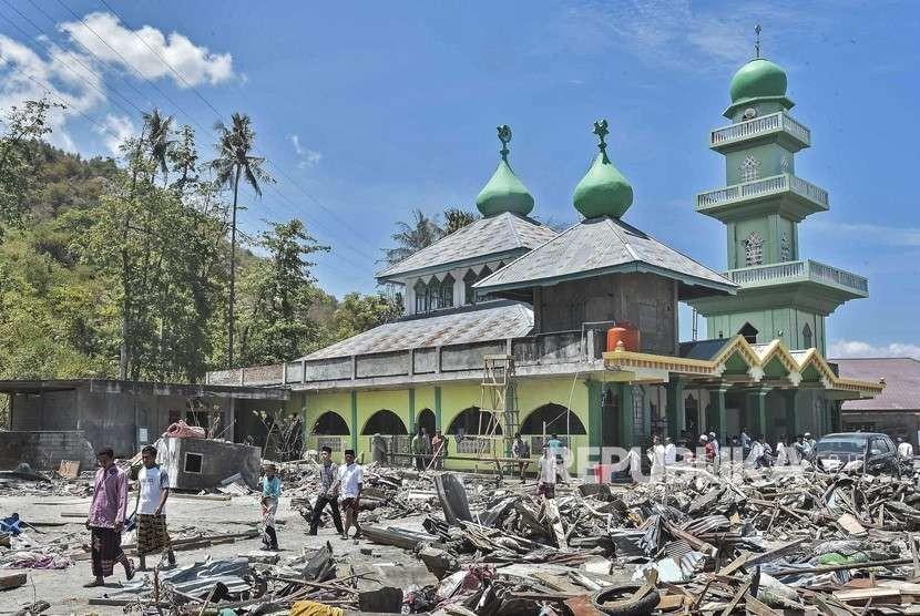Warga korban gempa tsunami Palu berjalan usai melaksanakan ibadah shalat Jumat di Masjid Baitussalam di Desa Loli Saluran, Donggala, Sulawesi Tengah, Jumat (5/10).