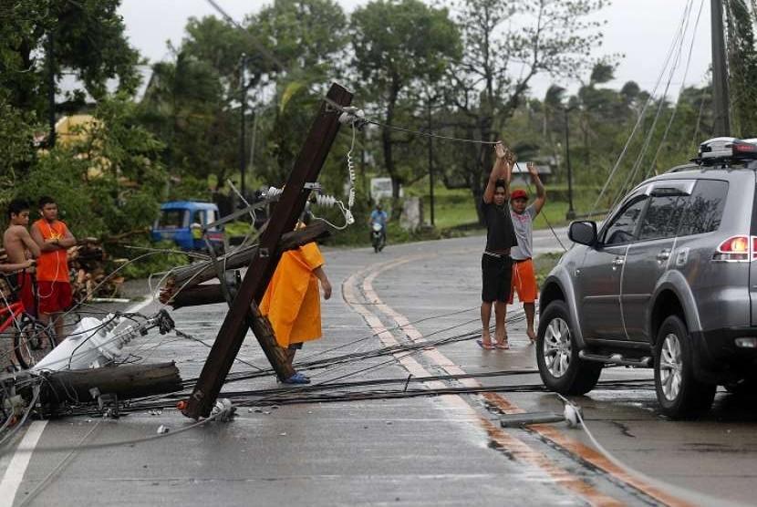 Warga Kota Lal-lo, Provinsi Cagayan, Filipina, berusaha menyingkirkan tiang listrik yang roboh menghalangi jalan akibat Topan Mangkhut, Sabtu (15/9).