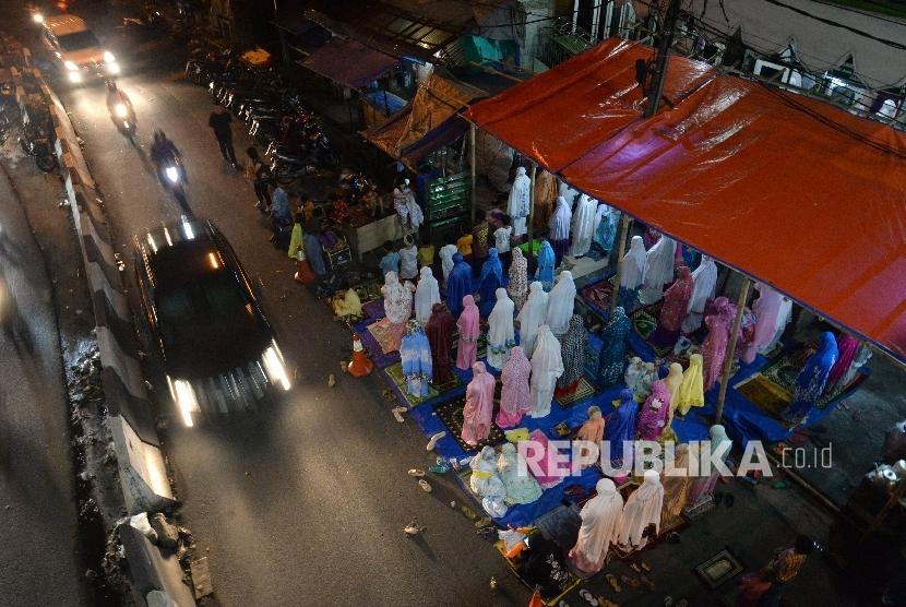 Warga melaksanakan shalat tarawih hingga bahu jalan di Kawasan Pasar Gembrong, Jakarta, Senin (29/5).