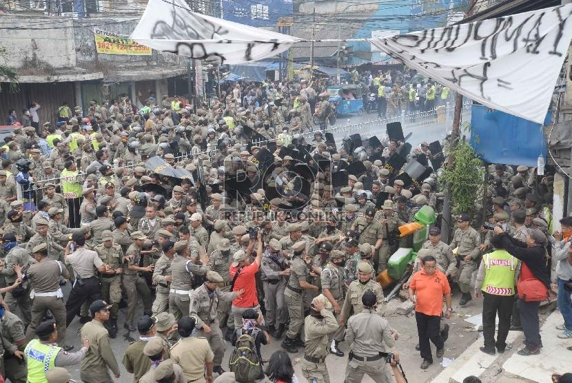 Warga melakukan perlawanan saat Satpol PP melakukan penggusuran pemukiman liar di Kampung Pulo, Jatinegara, Jakarta, Kamis (20/8).   (Republika/Yasin Habibi)
