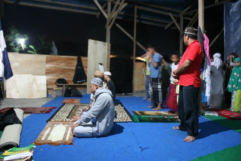 Warga melakukan shalat berjamaah di mushala sementara pengganti Mushola Asy Syuhada