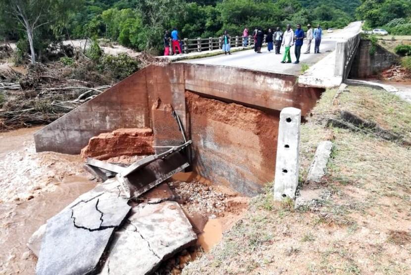 Warga melihat kerusakan di jembatan akibat Badai Idai di Chimanimani, Zimbabwe, Ahad (17/3).