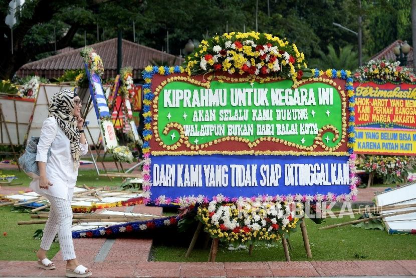 Warga melintas di antara karangan bunga yang ditujukan untuk Gubernur DKI Jakarta Basuki Tjahaja Purnama atau Ahok dan Wakil Gubernur Djarot Saiful Hidayat di halaman kantor Balai Kota Jakarta, Rabu (26/4)