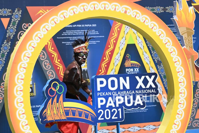 Warga melintas di dekat papan pernak-pernik PON Papua di kawasan Pasar Lama Timika, Kabupaten Mimika, Papua (ilustrasi).