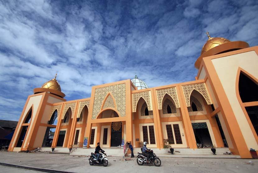 Warga melintas di depan Masjid Agung Syekh Burhanuddin, di Ulakan, Padangpariaman, Sumatera Barat, Kamis (18/12).