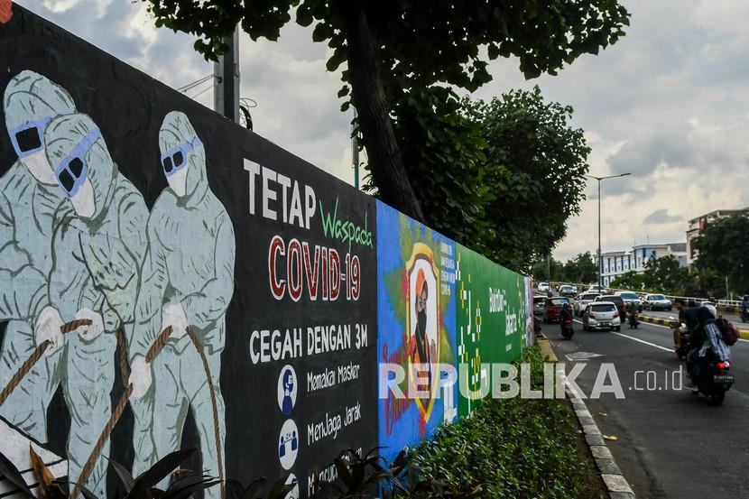 Warga melintas di depan mural tentang pandemi COVID-19 di Kawasan Tebet, Jakarta, Selasa (15/9/2021). Gubernur DKI Jakarta Anies Baswedan memperpanjang masa pemberlakuan pembatasan kegiatan masyarakat (PPKM) berbasis mikro selama dua pekan atau hingga 28 Juni 2021, hal tersebut dilakukan karena penyebaran COVID-19 di Jakarta dalam kondisi yang memerlukan perhatian ekstra.