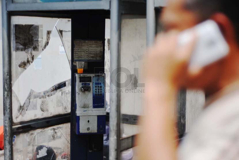 Warga melintas di depan telepon umum koin di kawasan Sudirman, Jakarta Selatan, Senin (13/10).(Republika/Raisan Al Farisi)