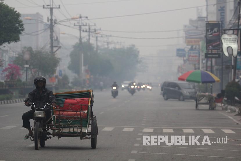 Warga melintas di jalan yang berkabut asap dari kebakaran hutan dan lahan di Kota Dumai, Dumai, Riau, Jumat (15/2/2019).