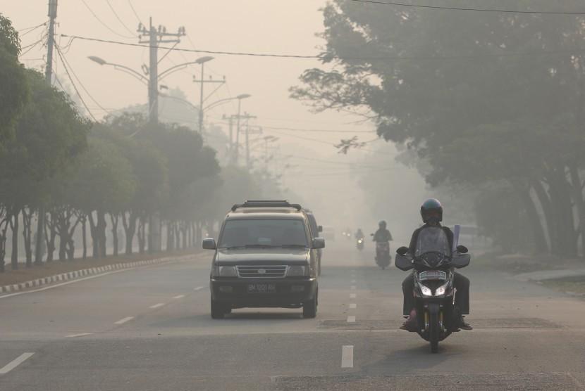Kabut Asap Karhutla: Warga melintas di jalan yang berkabut asap pekat dari kebakaran hutan dan lahan (karhutla) di kota Dumai, Dumai. Riau, Sabtu (23/2/2019).