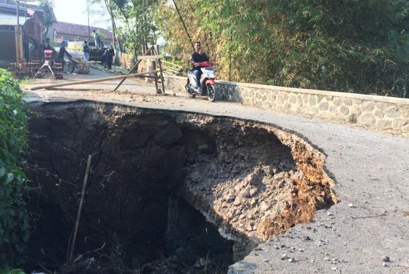 Warga melintas di jembatan amblas di Desa Karangsembung, Kecamatan Jamanis, Kabupaten Tasikmalaya, Rabu (14/8). Telah tiga bulan jembatan itu amblas tapi belum ada perbaikan hingga saat ini.