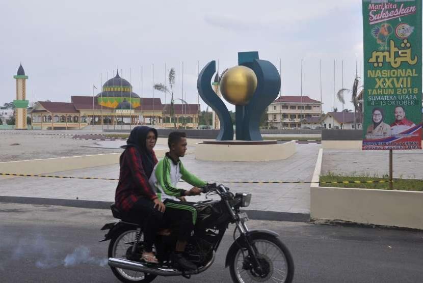 Warga melintas di lokasi kawasan Musabaqah Tilawatil Quran (MTQ) XXVII/2018 di Medan, Sumatera Utara, Jumat (14/9).