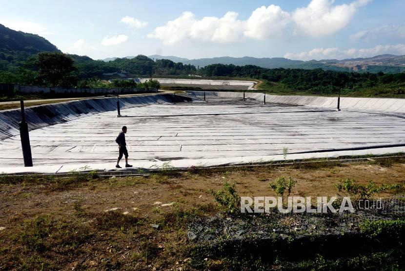 Warga melintas di Tempat Pengolahan dan Pemrosesan Akhir Sampah (TPPAS) Lulut Nambo yang belum beroperasi di Kelapa Nunggal, Kabupaten Bogor, Jawa Barat, Senin (9/4).