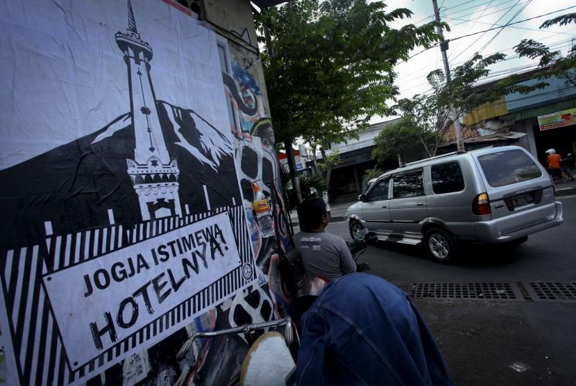 Warga melintas didekat poster yang bertuliskan