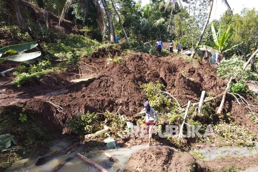 Warga melintasi area longsor di Pakel, Licin, Banyuwangi, Jawa Timur, Kamis(17/6/2021). Longsor yang terjadi akibat hujan deras yang mengguyur daerah tersebut pada Rabu (16/6/2021) sore itu mengakibatkan dua rumah tertimbun material longsor dan mengakibatkan satu orang korban meninggal dunia.