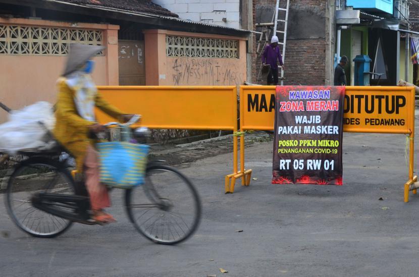 Warga melintasi jalan desa yang ditutup akibat karantina wilayah di Desa Pedawang, Kudus, Jawa Tengah, Selasa (1/6/2021). Akibat lonjakan tajam kasus COVID-19 pascalebaran di kabupaten itu, sebanyak 42 desa masuk zona merah COVID-19 dan menerapkan aturan Pemberlakuan Pembatasan Kegiatan Masyarakat (PPKM) skala mikro untuk mencegah penularan COVID-19.