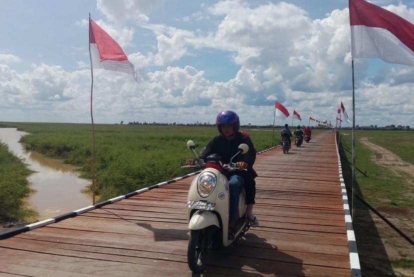 Warga melintasi jembatan penghubung Desa Sebemban dan Desa Melintang di Kecamatan Muara Wis, Kabupaten Kutai Kartanegara,Provinsi Kalimantan Timur pada Selasa (13/11). Jembatan dibangun lewat program TMMD.