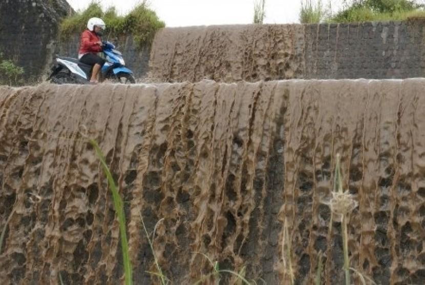 Warga melintasi luapan lahar dingin material Gunung Kelud di Kali Badak, Desa Gambar Kecamatan Nglegok, Kabupaten Blitar, pertengahan, Februari lalu. Saat ini lahar beku yang terbentuk di Blitar menjadi obyek wisata. (Ilustrasi)