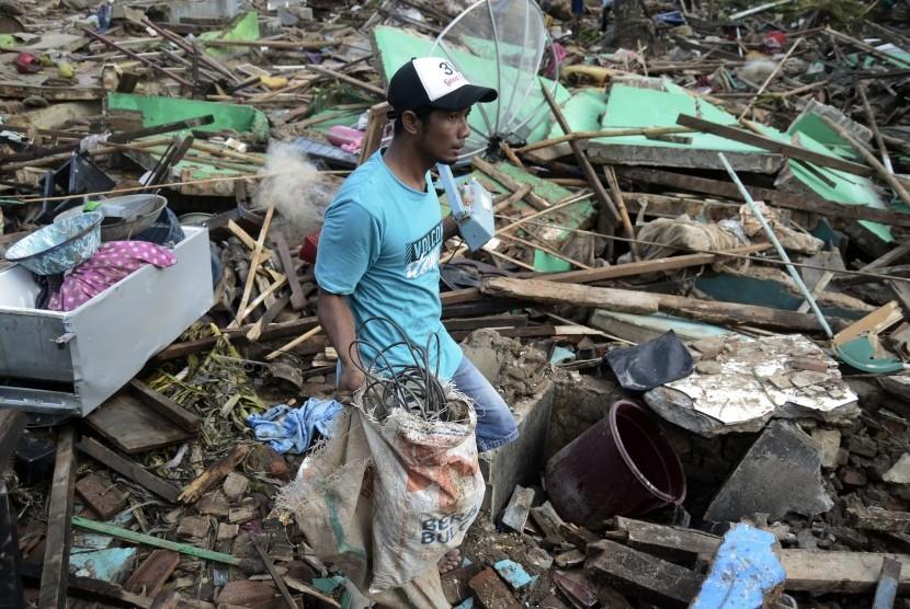 Warga melintasi reruntuhan rumah yang rusak akibat tsunami di Desa Kunjir, Kecamatan Rajabasa, Lampung Selatan, Lampung, Jumat (28/12/2018).