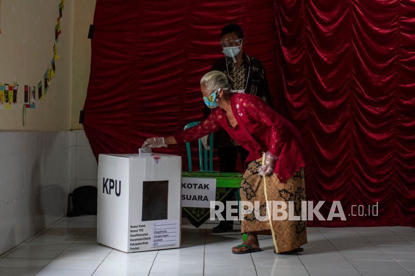 Warga memasukkan surat suara di Tempat Pemungutan Suara (TPS) 8 Kalitengah Lor di Barak Pengungsian Glagaharjo, Cangkringan, Sleman, DI Yogyakarta, Rabu (9/12/2020). Warga Dusun Kalitengah Lor yang berada di Kawasan Rawan Bencana (KRB) Gunung Merapi melakukan pemungutan suara Pilkada Bupati dan Wakil Bupati Sleman 2020 di barak pengungsian Desa Glagaharjo.
