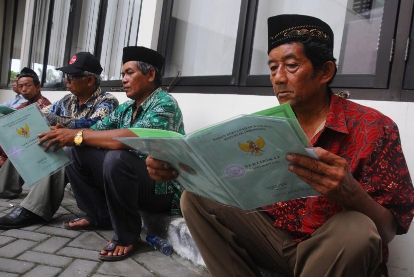 Warga membaca dokumen sertifikat tanah yang diperoleh dari Pemerintah melalui Badan Pertanahan Nasional (BPN) di Boyolali, Jawa Tengah, Jumat (21/4).
