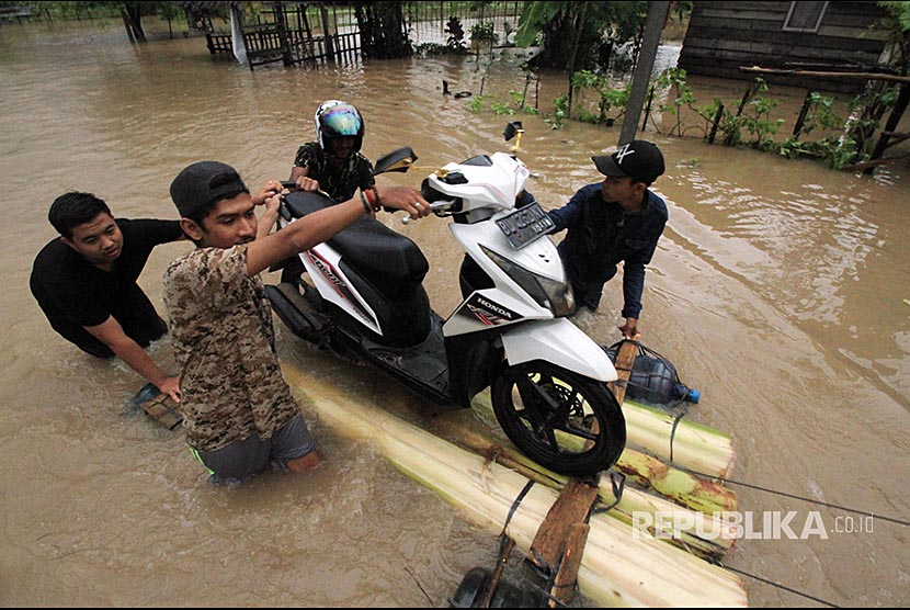 Residents help evacuation of motorcycles to pass through floods in Cot Girek Kandang, Muara Dua, Lhokseumawe, Aceh, on Friday (December 1).