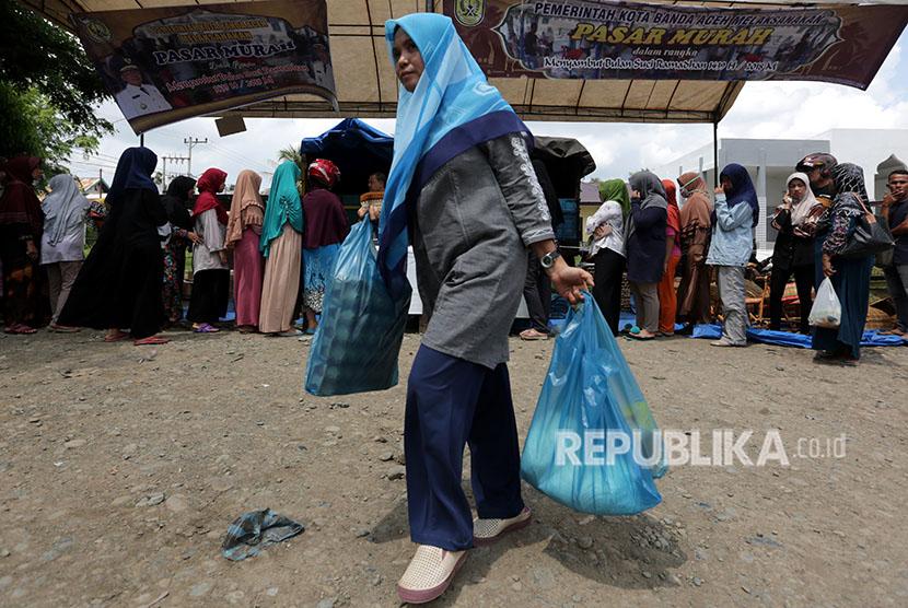 Warga membawa kebutuhan pokok seusai berbelanja di pasar murah (ilustrasi)