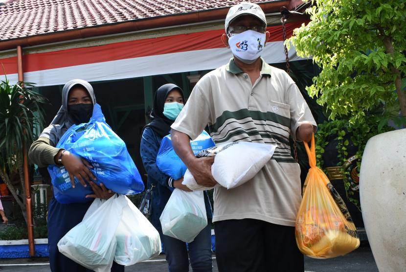 Warga membawa paket bantuan bahan pokok seusai penyerahan bantuan sosial di Pendopo Muda Graha, Kabupaten Madiun, Jawa Timur, Senin (2/8/2021). Pemkab Madiun membagikan bantuan sosial bahan pokok kepada 810 anak yatim piatu, 525 orang penyandang disabilitas, 60 orang eks penyandang psikotik dan 100 orang lanjut usia guna meringankan beban saat pandemi COVID-19.