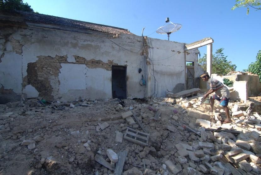 Warga membersihkan puing bangunan yang ambruk akibat gempa di Desa Bula'an, Sumenep, Jawa Timur, Kamis (14/6).
