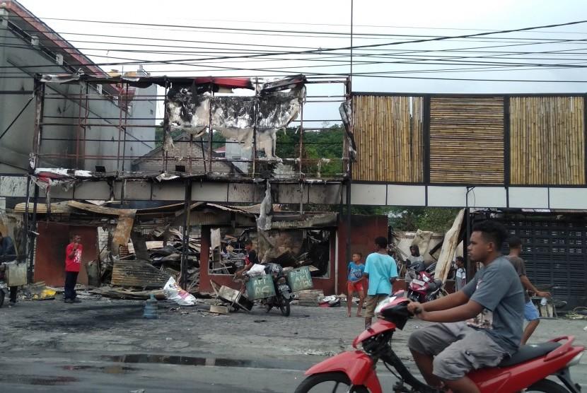 Warga membersihkan puing sisa kerusuhan di salah satu gedung yang terbakar di Manokwari, Papua Barat, Selasa (20/8/2019). Pascakerusuhan yang terjadi pada Senin (19/8), kondisi Manokwari sudah kondusif dan warga mulai melakukan aktivitas di ruang publik.
