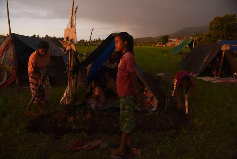 Warga membuat parit di sekililing tenda darurat yang mereka bangun di pematang sawah di Tanjung, Lombok Utara, Jawa Timur, Kamis (9/8).