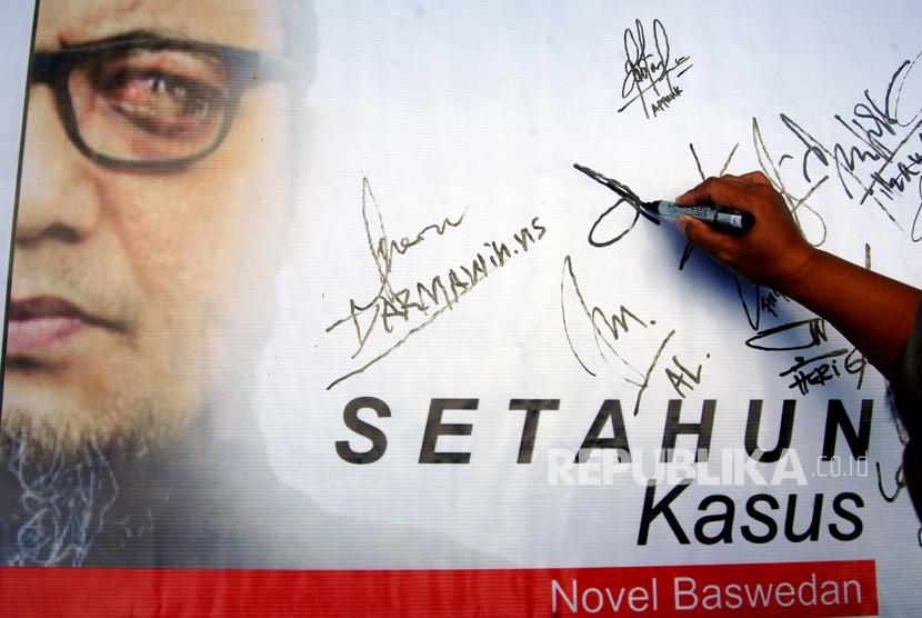 Warga membubuhkan tanda tangan di poster saat aksi memperingati setahun kasus penyiraman air keras terhadap Novel Baswedan