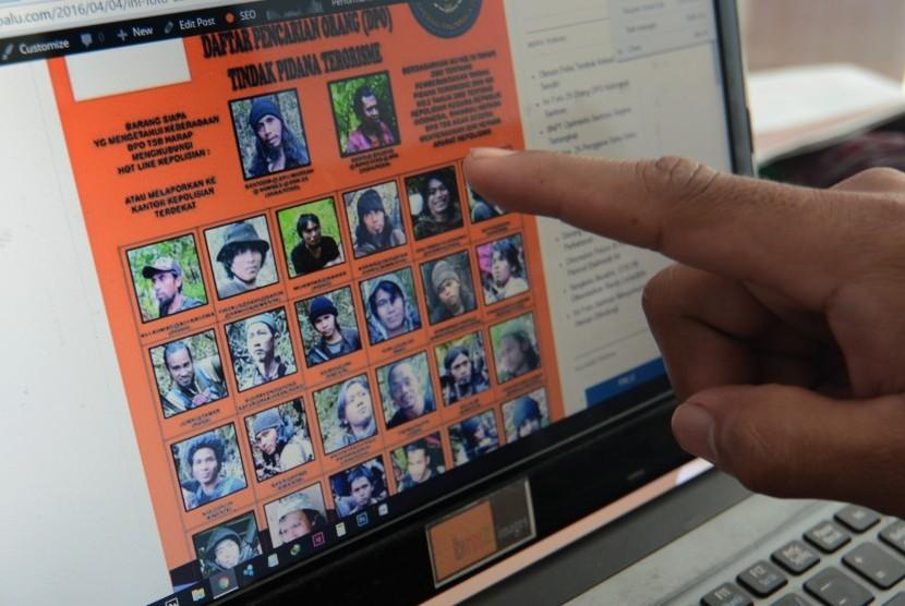 Warga membuka laman yang menampilkan Daftar Pencarian Orang (DPO) teroris Poso di Palu, Sulawesi Tengah.