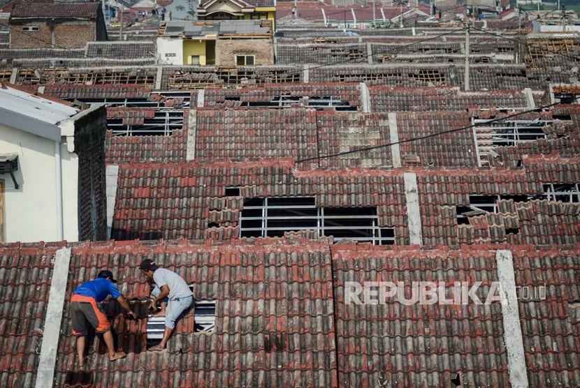 Warga memperbaiki atap rumahnya yang rusak akibat angin puting beliung di Perumahan Rancaekek Permai 2, Kabupaten Bandung, Jawa Barat, Sabtu (12/1/2019).
