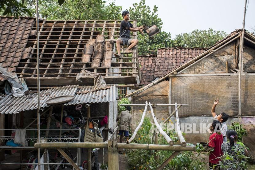 Warga memperbaiki atap rumahnya yang rusak akibat angin puting beliung di Kampung Pasirpeuti, Sukaluyu, Kabupaten Cianjur, Jawa Barat, Sabtu (12/01/2019).