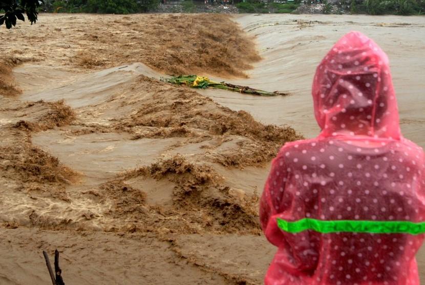 Warga memperhatikan aliran sungai Jeneberang yang meluap di Kabupaten Gowa, Sulawesi Selatan, Selasa (22/1/2019). Meluapnya sungai Jeneberang akibat curah hujan yang tinggi membuat sejumlah daerah di Kabupaten Gowa terendam banjir.