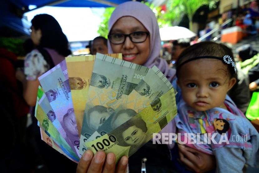 Warga memperlihatkan lembaran uang baru yang baru ditukarnya di kas keliling, Di Pasar Baru, Jalan Otto Iskandardinata, Kota Bandung, Selasa (20/12).
