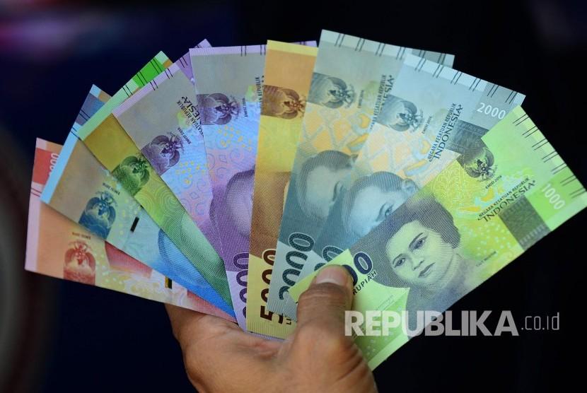 Warga memperlihatkan lembaran uang baru yang baru ditukarnya di kas keliling, ilustrasi