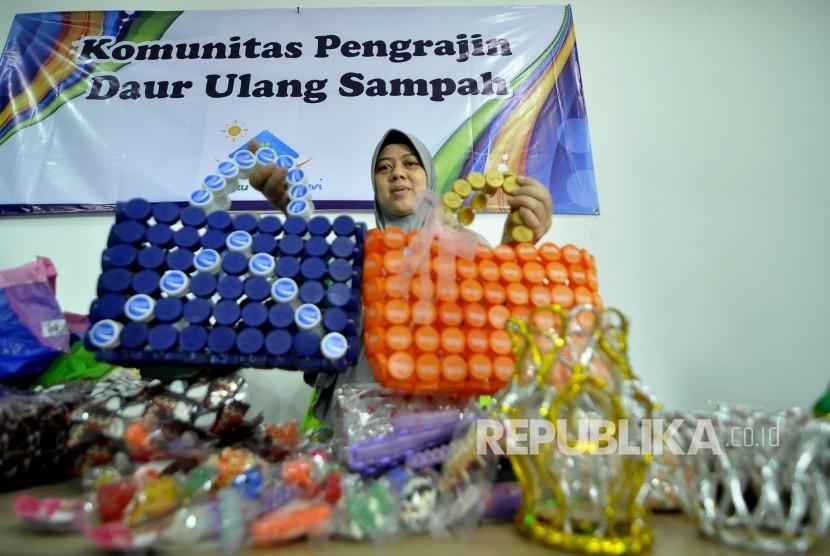 Warga memperlihatkan produk tas hasil dari daur ulang tutup botol minuman kemasan saat peresmian Bank Sampah Induk Kota Bandung dan Ecomart di Jalan Ahmad Yani, Kota Bandung, Selasa (21/2).