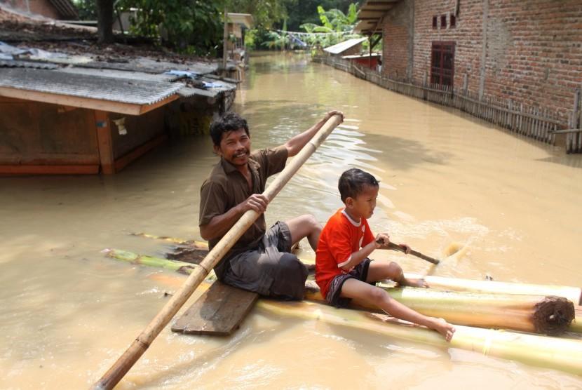 Warga mendayung perahu buatan saat berusaha keluar dari rumahnya yang terendam banjir di kawasan pemukiman penduduk bantaran Sungai Citarum, Kedungwaringin, Kabupaten Bekasi, Jawa Barat, Senin (14/11).
