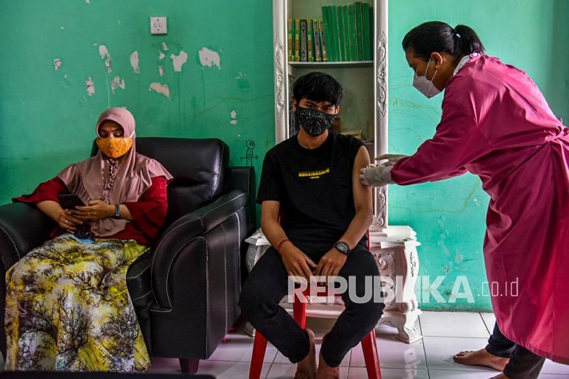 Warga menerima suntikan vaksin di rumahnya saat pelaksanaan vaksinasi COVID-19 dari pintu ke pintu (door to door) di Medan Helbetia, Medan, Sumatera Utara, Rabu (14/7/2021). Untuk mengurangi mobilitas warga di masa PPKM Darurat, Badan Intelijen Negara (BIN) menggelar vaksinasi COVID-19 dengan skema door to door ke rumah warga dengan target 1.000 orang per hari.