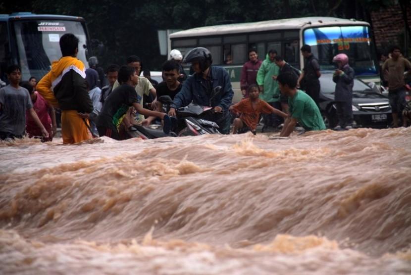 Warga menerobos banjir yang menggenangi kawasan jalan Sudirman, Jakarta, Kamis (17/1).