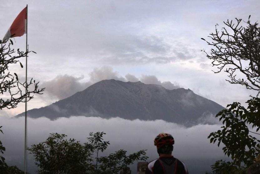 Warga mengamati asap yang mengepul dari kawah Gunung Agung di Pos Pemantauan Gunungapi Agung, Rendang, Karangasem, Bali, Selasa (3/7).