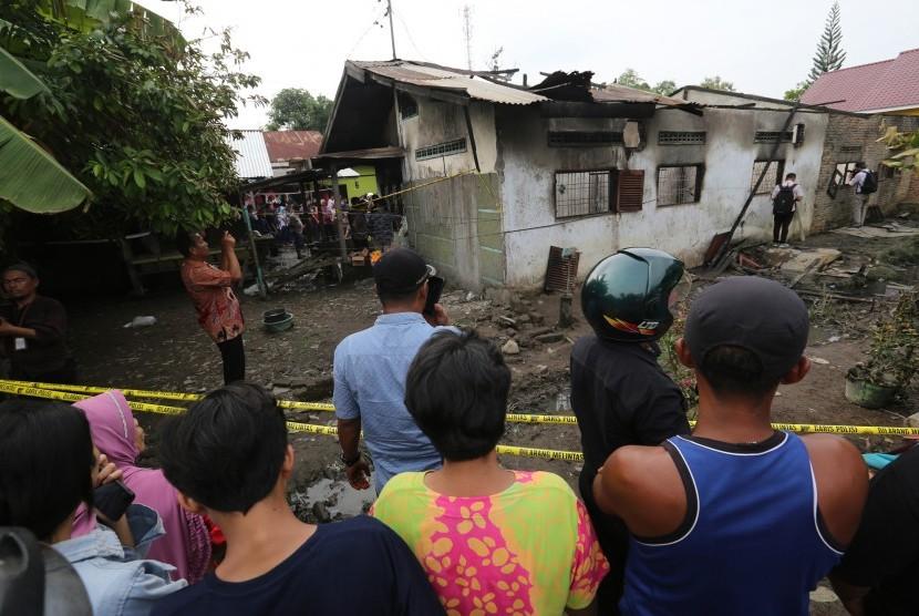 Warga mengamati lokasi kebakaran pabrik korek gas (mancis) di Desa Sambirejo, Kecamatan Binjai, Sumatera Utara, Jumat (21/6/2019).
